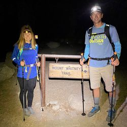 Kim and Jared White stand together with headlamps shining at the Mount Whitney trailhead. Their hike started at 3:30 a.m.