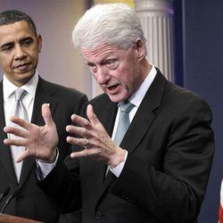 President Barack Obama listens to former President Bill Clinton speak in the White House briefing room.