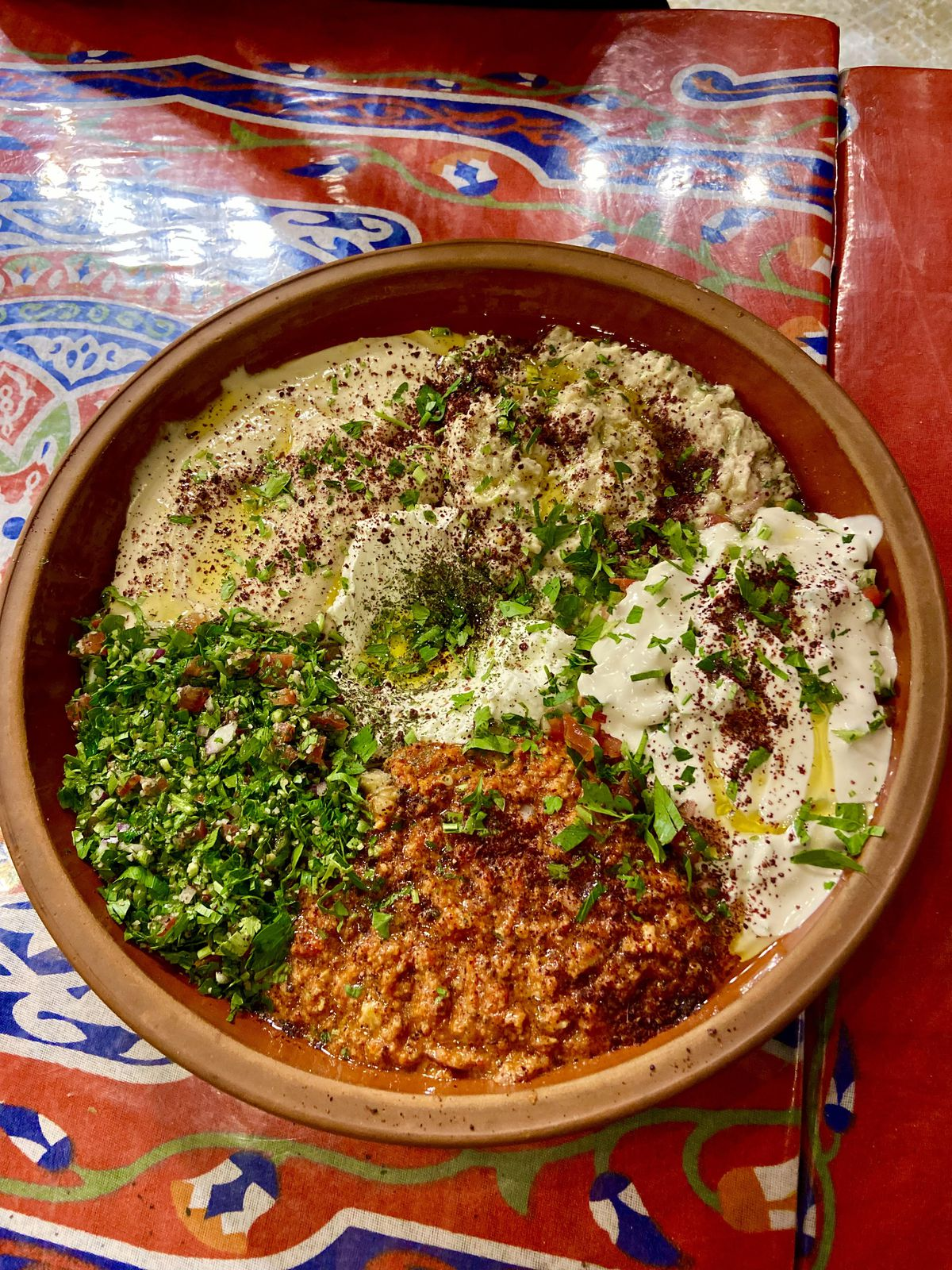 The colorful mezze platter of hummus, baba ganoush, muhammarah, tahini, tabouleh, labnedusted with sumac is presented in a clay bowl ontop of a colorful tablecloth.