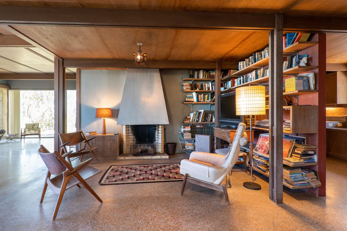 Three chairs are arranged around a cement fireplace with book shelves on the right.