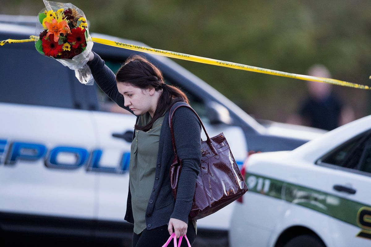 A woman holds flowers near Umpqua Community College in Oregon.