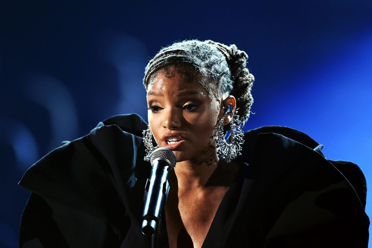 a young black woman, Halle Bailey, sings into a microphone
