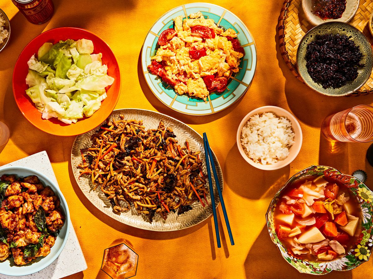 An overhead shot of a spread of colorful dishes laid out on a sunny yellow table