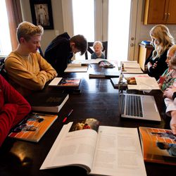 """The Kirby family, from left to right, Trevor, Jacob, Mason, Carly, Kristin, Camree and Ryan, prays before beginning a gospel study at home using """"Come, Follow Me — For Individuals and Families: Book of Mormon 2020,"""" a manual for The Church of Jesus Christ of Latter-day Saints, in Lehi on Sunday, March 15, 2020."""