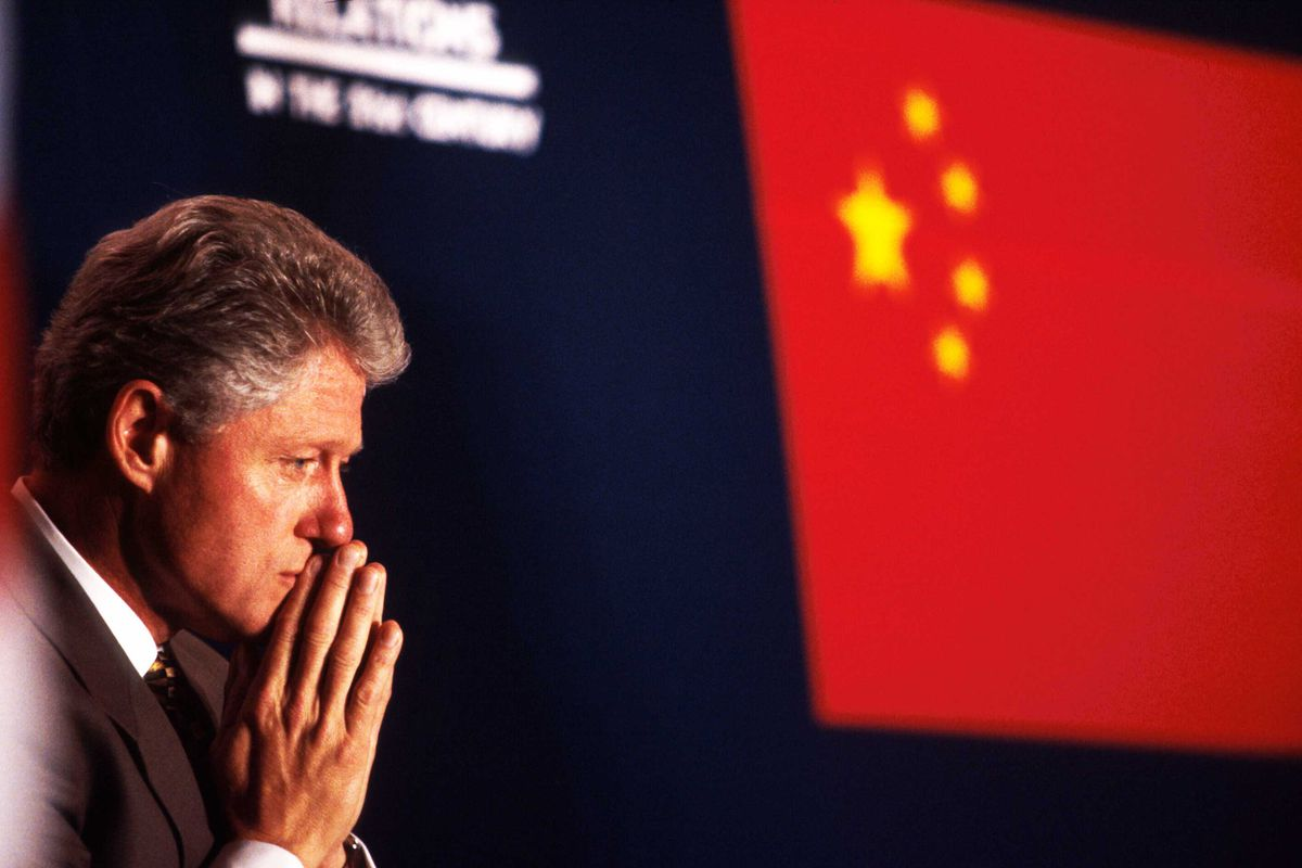 Bill Clinton sits in front of the Chinese flag.
