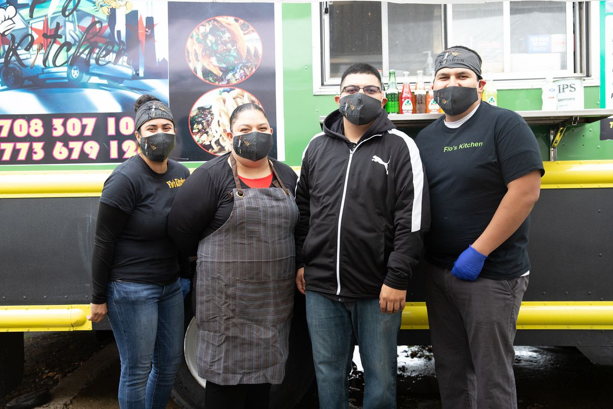 Four family members with masks pose in front of a green food truck.