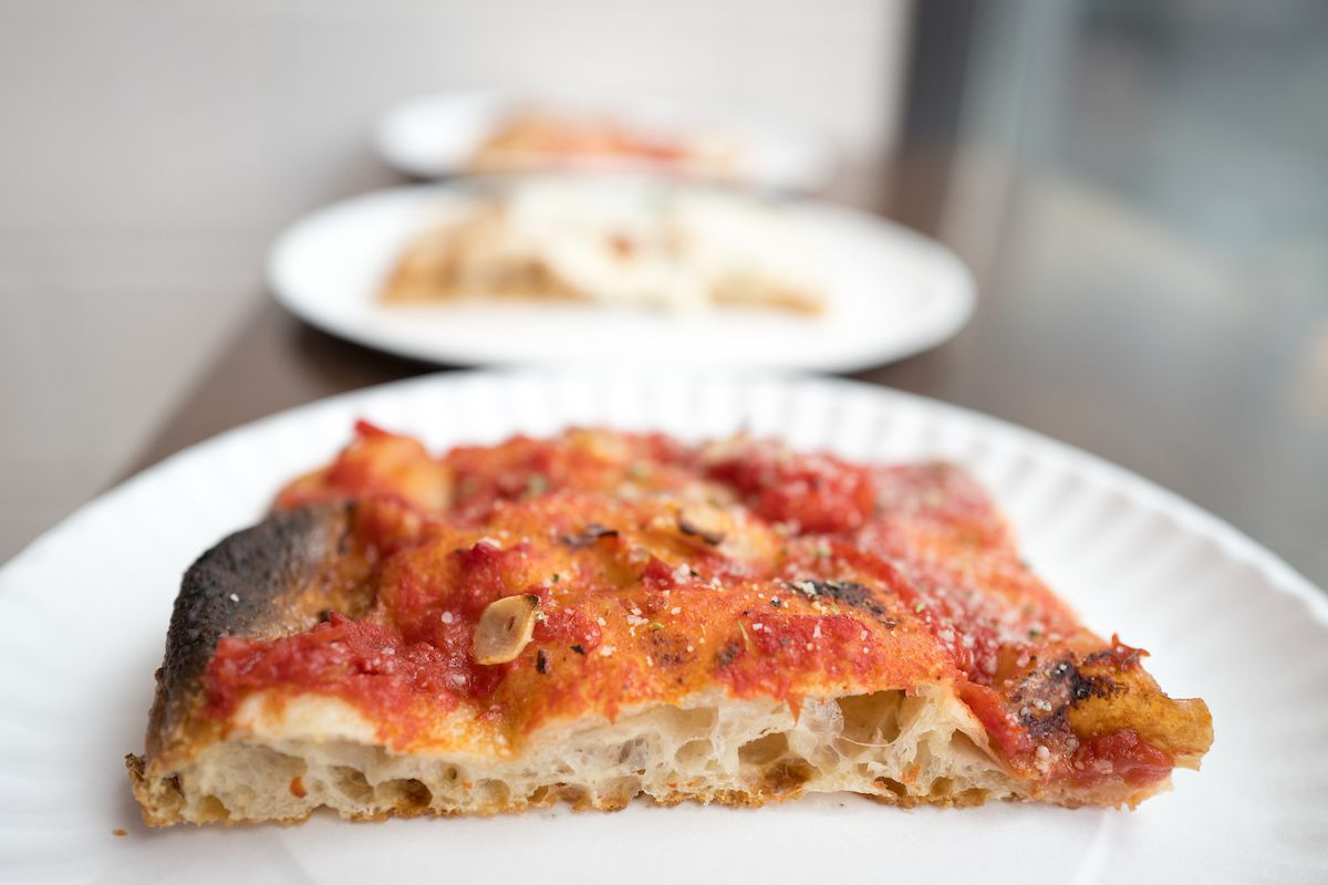 A tomato slice lies on a white paper plate at Corner Slice