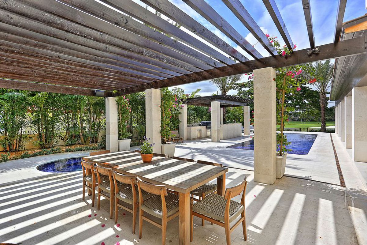 The backyard at 1244 Anastasia Avenue in Coral Gables, showing a jacuzzi, outdoor dining area, and a pool, in addition to a summer kitchen