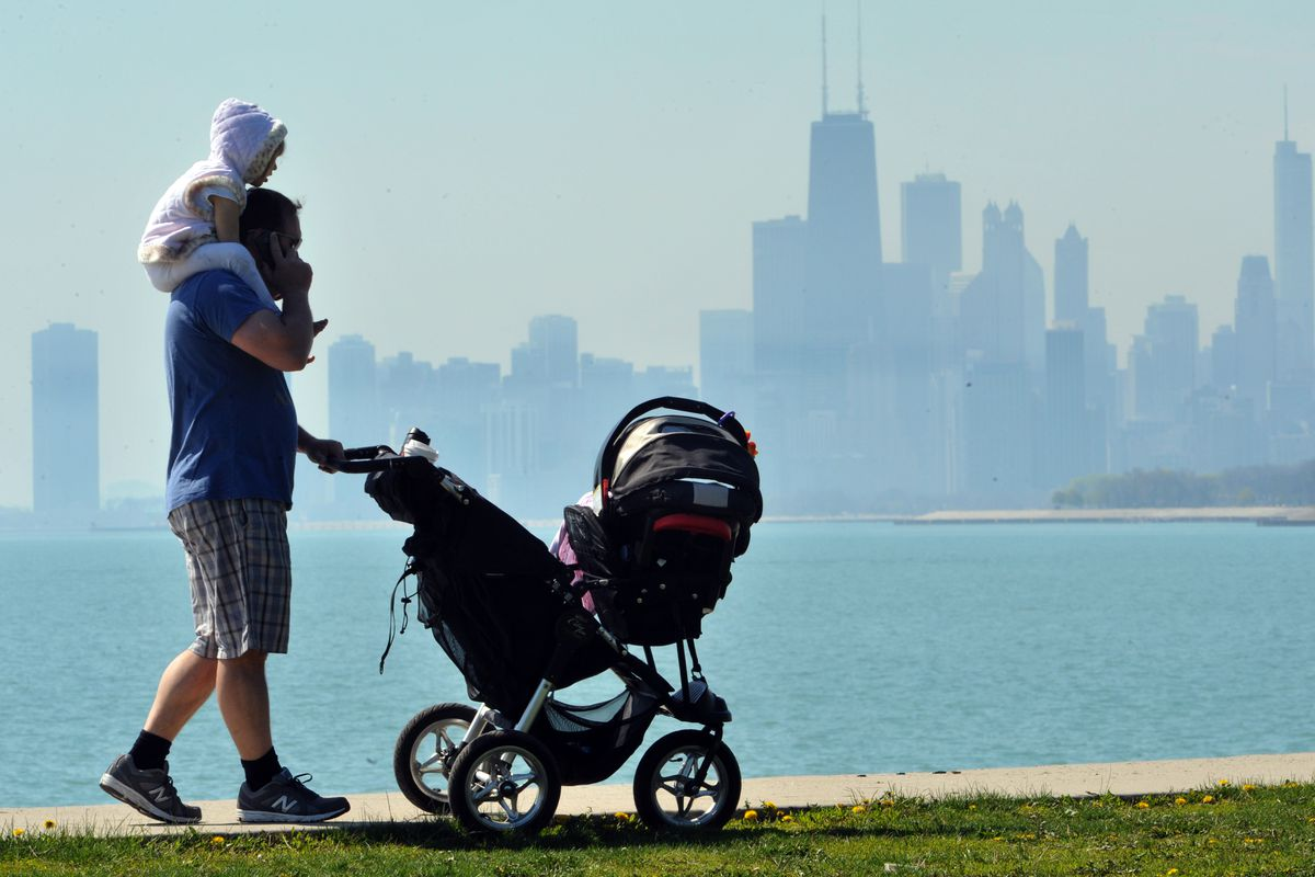 A father juggles pushing a stroller and his two-year-old daughter at Montrose Harbor in 2013.