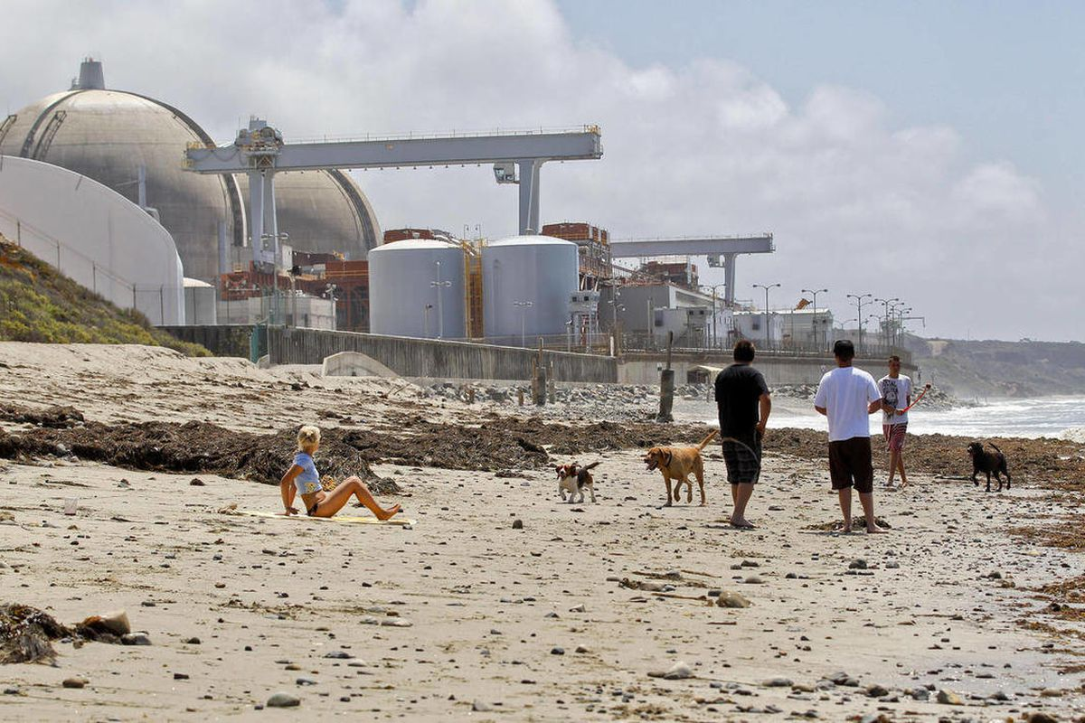 In this Friday, April 27, 2012, file photo, people utilize the beach outside the San Onofre Nuclear Generating Station in San Onofre, Calif.