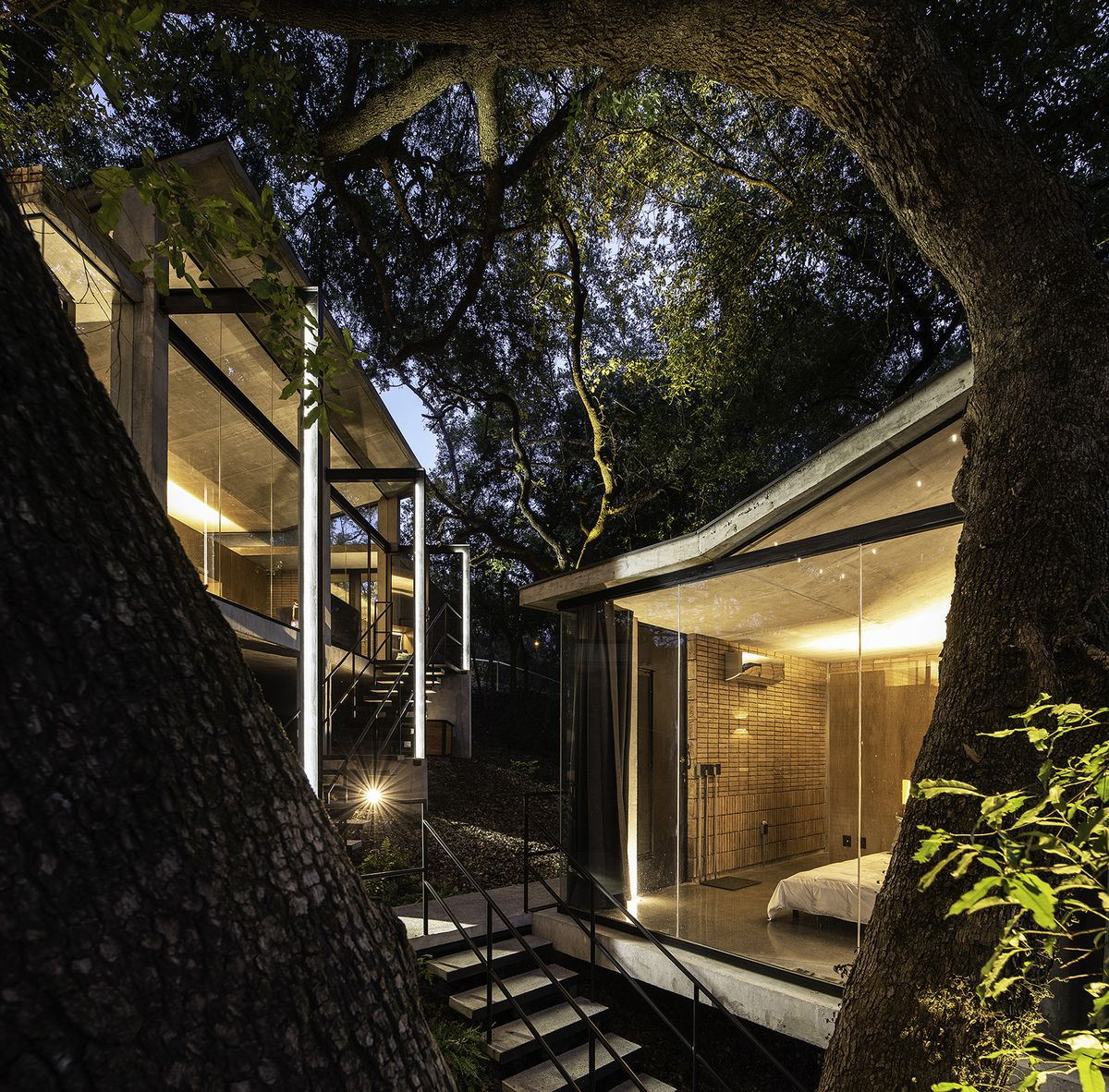 Modern house lit up at night. The buildings are treehouse style, with big glass windows and a metal staircase in between.