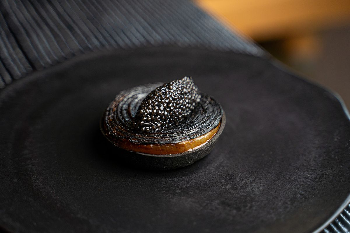 A thick charred slice of onion topped with caviar.
