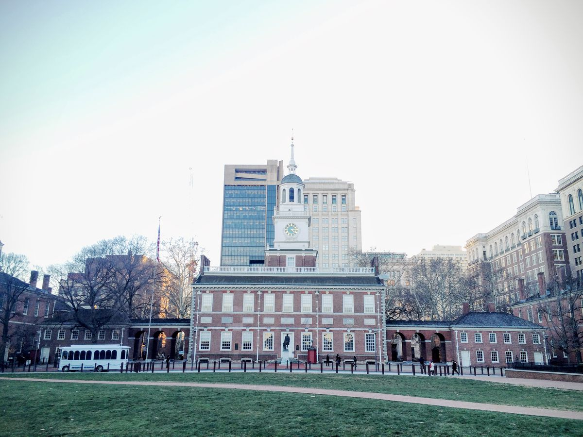 The exterior of Independence Hall. The facade is red brick. There is a lawn in front.