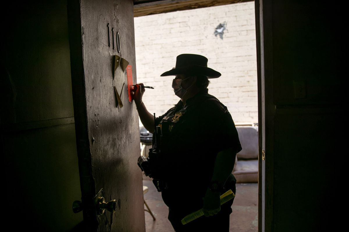 The constable signing an eviction order posted on a door.
