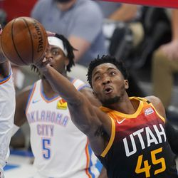 Utah Jazz guard Donovan Mitchell (45) shoots in front of Oklahoma City Thunder guard Luguentz Dort (5) and forward Darius Bazley, left, during the first half of an NBA basketball game in Oklahoma City, Monday, Dec. 28, 2020.