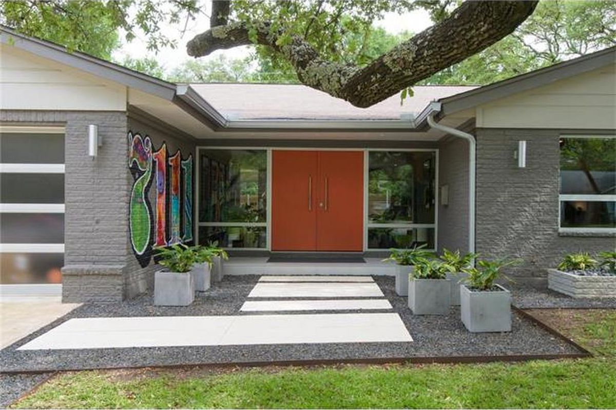 tight shot of exterior entrance of gray brick midcentury modern with orange double door, big front windows, and giant graffiti-style address pained on one wall