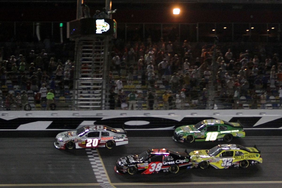 Joey Logano (20) crosses the finish line ahead of Jason Leffler (38), Kyle Busch (18) and Reed Sorensonto take the checkered flag and win the NASCAR Nationwide Series Subway Jalapeno 250 at Daytona International Speedway.