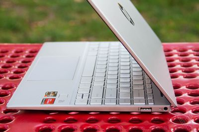 The HP Pavilion Aero 13 seen from the right, half open, on a red picnic table.