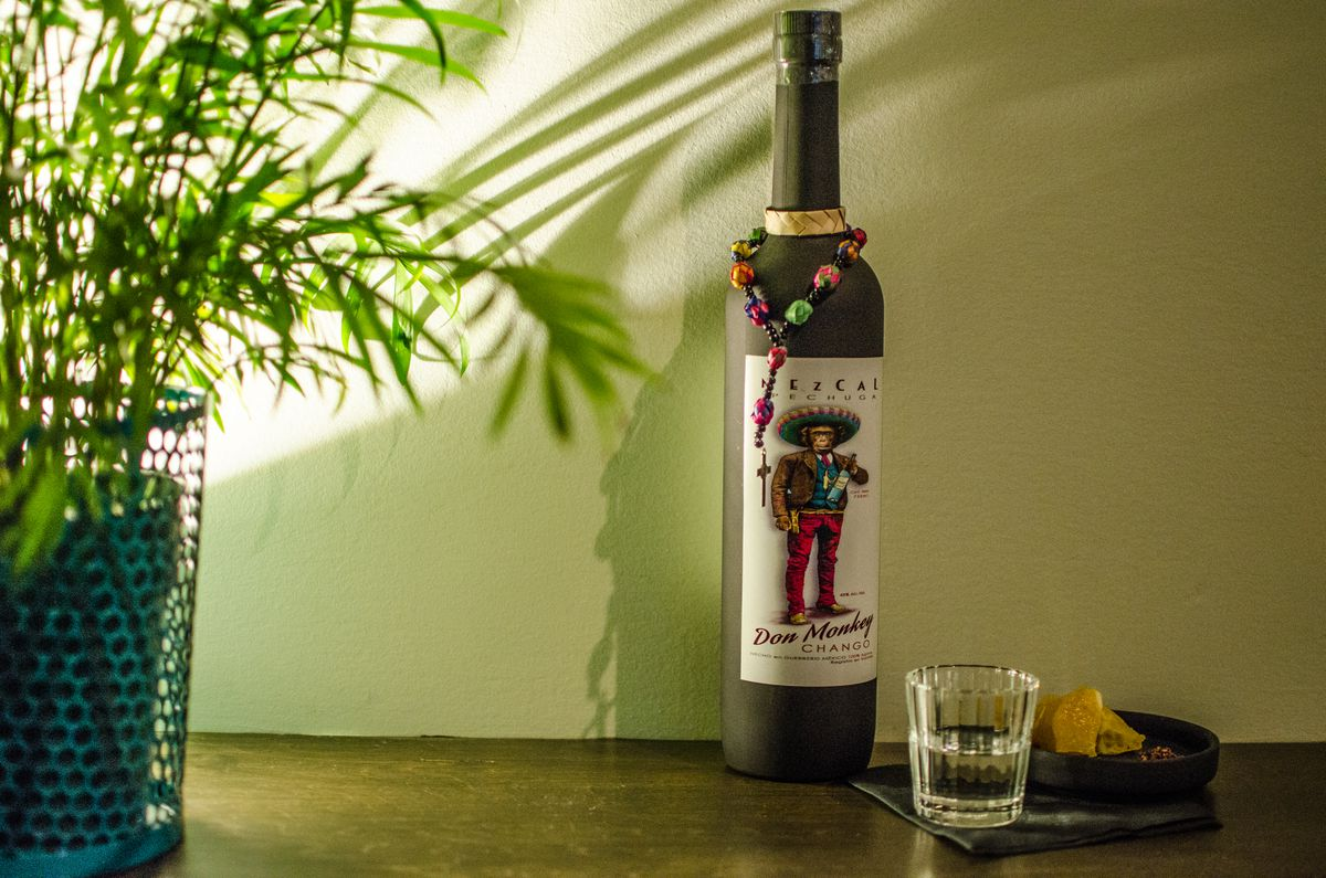 A bottle of mezcal, decorated with a monkey wearing a sombrero, sits next to a glass of it, along a wooden counter next to a potted plant.