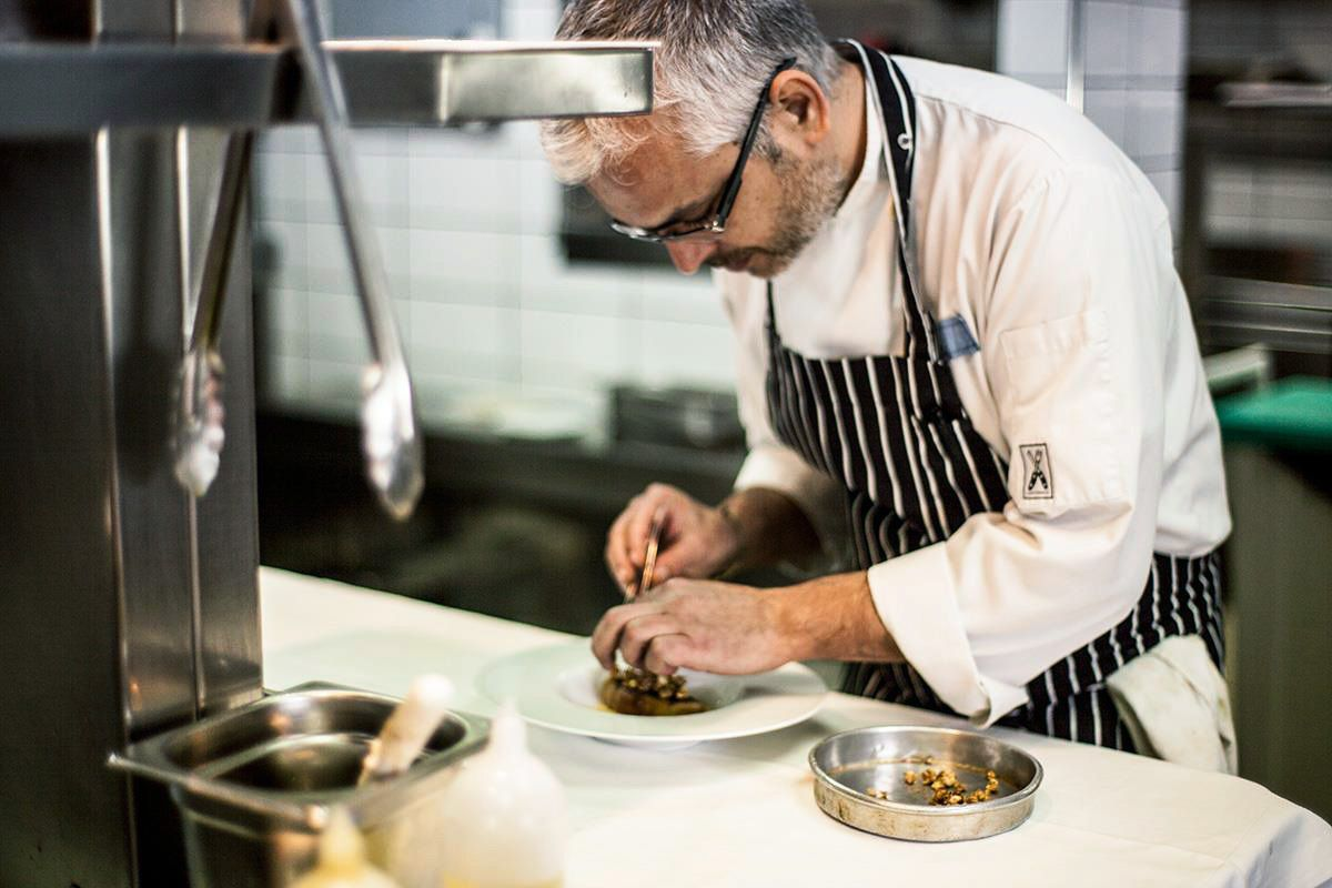 A chef in an apron delicately plates a dish in a restaurant kitchen