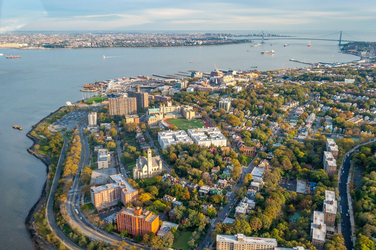 An aerial view of city buildings and trees along a waterfront.
