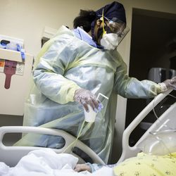 Nurse Jessica Bell gives a sip of water to a patient with COVID-19 and on a ventilator in the Intensive Care Unit at Roseland Community Hospital on the Far South Side, Tuesday afternoon, Dec. 8, 2020.