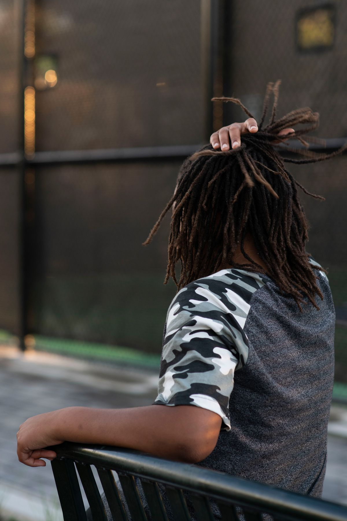 A Black boy sits on a park bench with his back toward the camera. He is touching his hair.