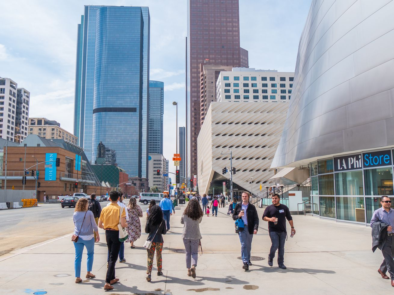 People walk on a sidewalk in Downtown LA. The Broad is in the background, along with the Museum of Contemporary Art.