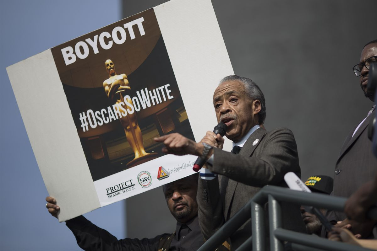 "Al Sharpton stands in front of a poster that reads ""Boycott #OscarsSoWhite"" and speaks into a microphone."
