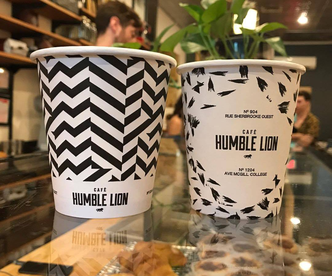 Two patterned paper cups with Humble Lion's logo.
