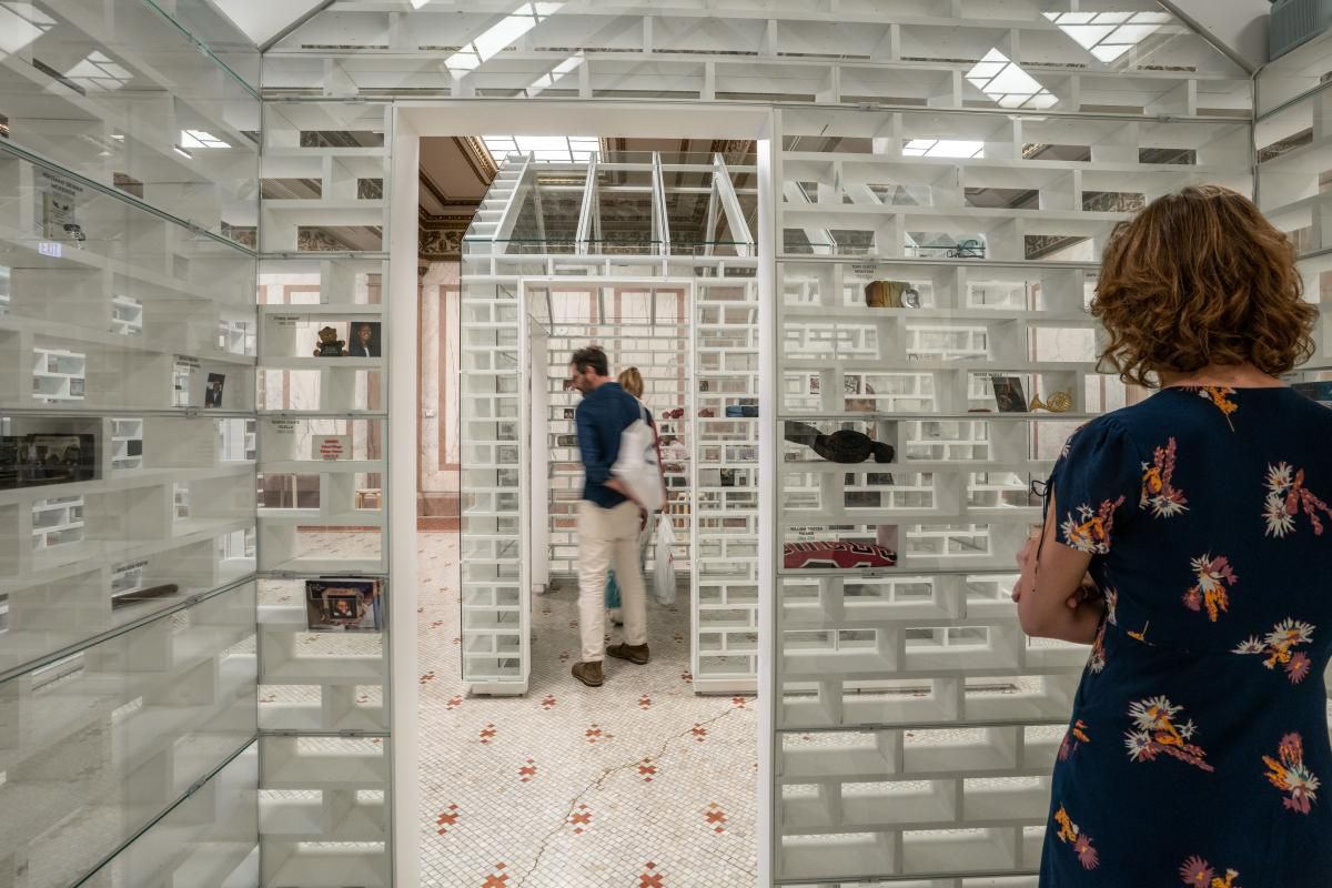 A woman stands inside a small white house made from hollow glass bricks filled with memory objects