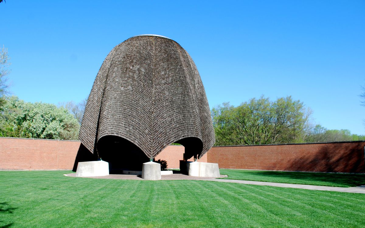 A brown, curving roof of an open-air church with concrete supports sits on a green grass with a brown wall behind it.