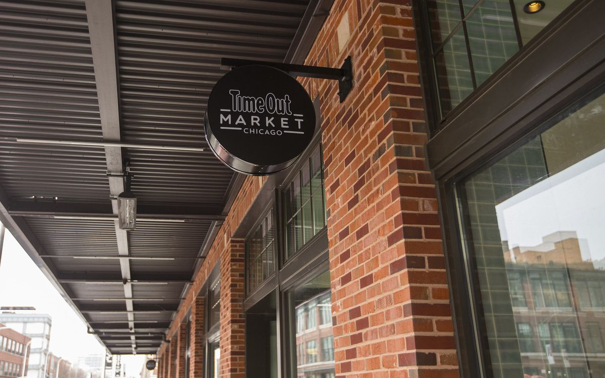"""The outside of a food hall with a sign reading """"Time Out Market."""""""