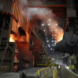 A giant ladle backs away after pouring its contents of red-hot iron into a vessel in the basic oxygen furnace as part of the process of producing steel.   AP Photo/Jeff Roberson