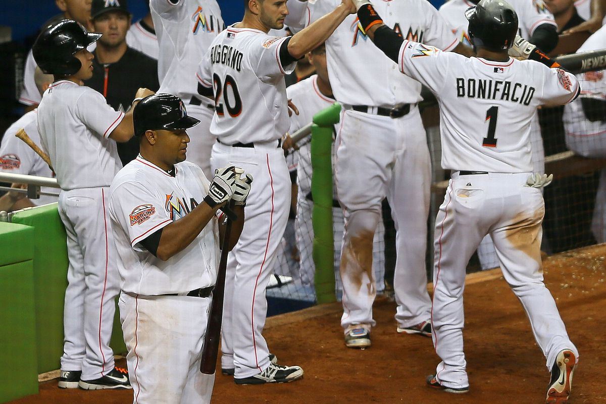 MIAMI, FL - JULY 16: Emilio Bonifacio #1 of the Miami Marlins is congratulated after a sacrifice bunt and an RBI during a game against the Washington Nationals at Marlins Park on July 16, 2012 in Miami, Florida.  (Photo by Mike Ehrmann/Getty Images)