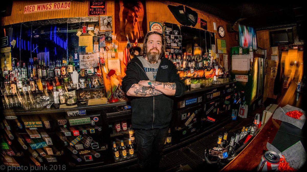 Jimmy Doom stands in front of a full bar of liquor bottles
