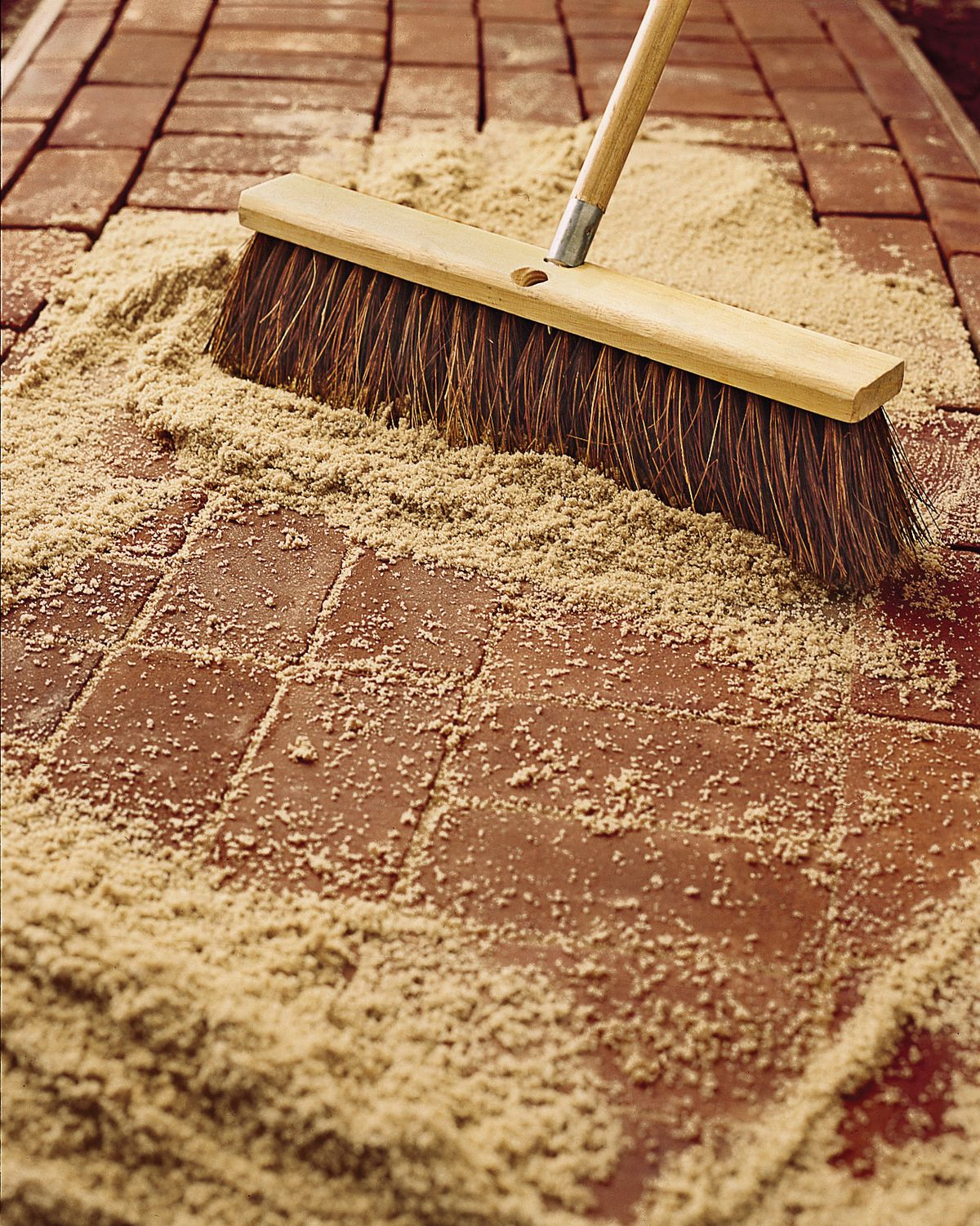 Man Uses Push Broom To Fill In Joints Of Bricks With Sand