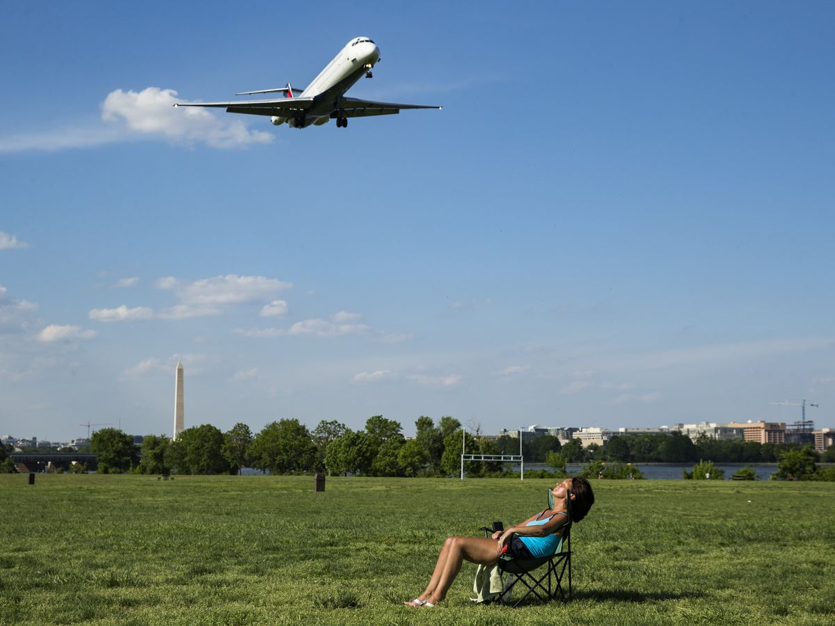 A person lounges in a chair in a large grassy field as an airplane flies overhead. In the distance are trees.