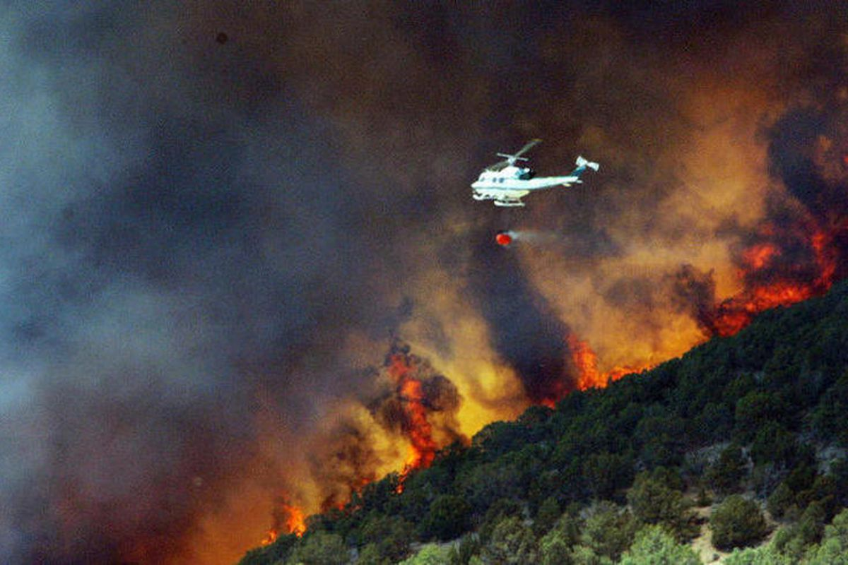 """FILE""""""""Emergency responders work on a wild land fire that is threatening homes in Saratoga Springs, Utah, Friday, June 22, 2012. About 1,000 homes are being evacuated after high winds kicked up a fire near a northern Utah dump. Fire officials were ca"""