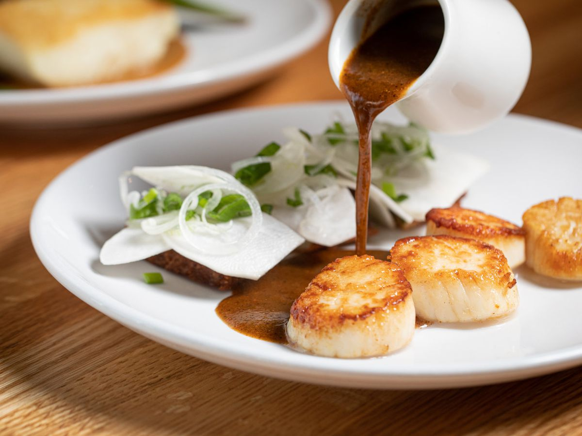 A plate of scallops with sauce poured on the side