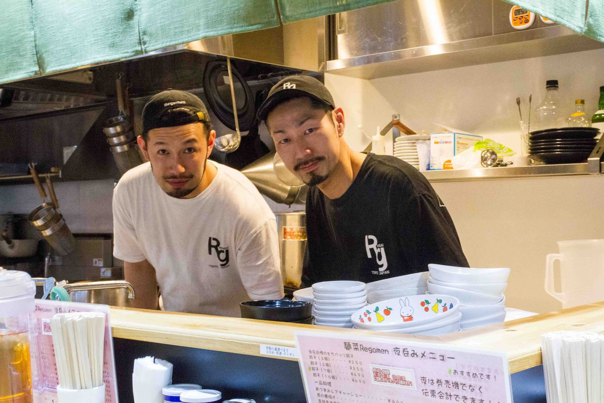 Two ramen chefs stand behind the counter.