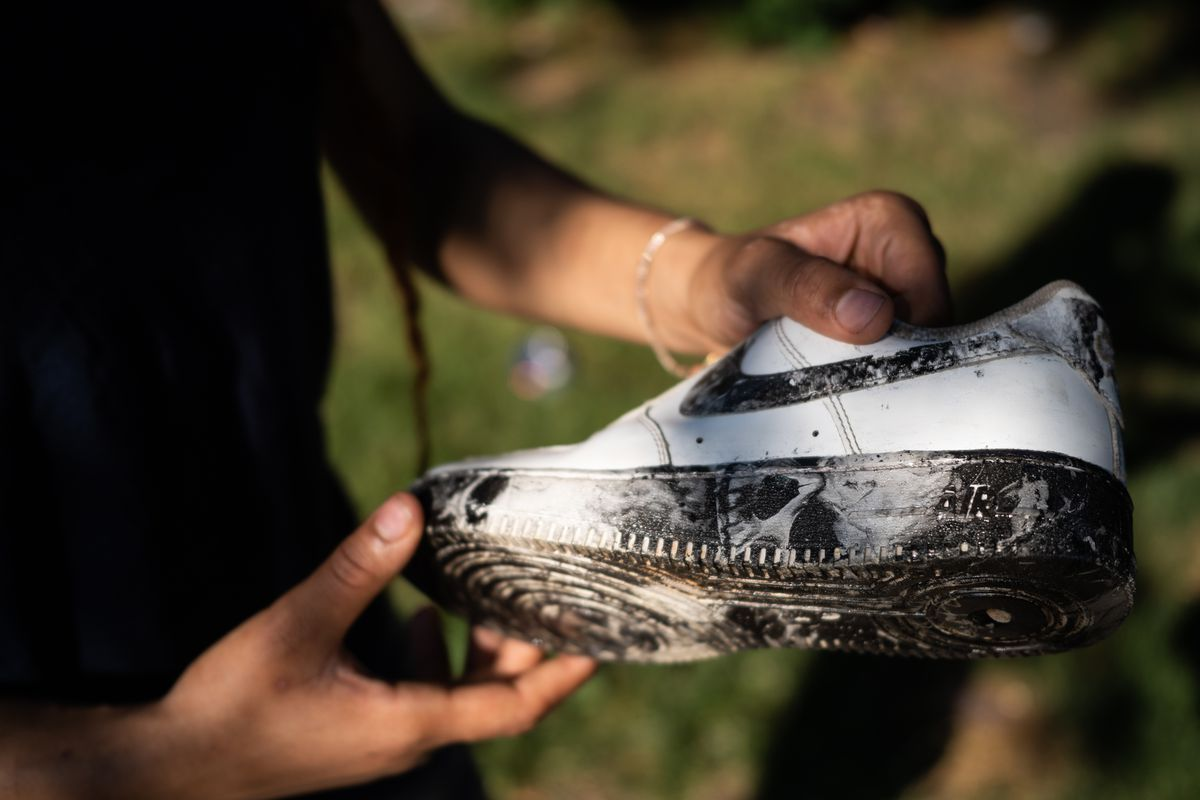 A young woman holds a black and white customized Nike shoe in the sunlight.