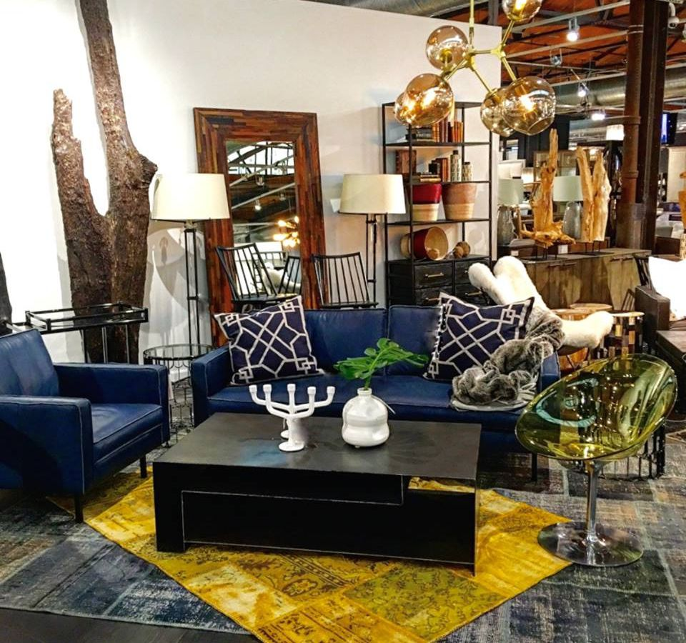 Inside a furniture store. There is a dark blue couch, a blue arm chair, a black coffee table, various light fixtures, and other items of furniture. A yellow and grey patterned area rug is under the coffee table.