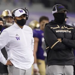 Washington coach Jimmy Lake, left, stands on the sideline during the first half of the team's NCAA college football game against Utah, Saturday, Nov. 28, 2020, in Seattle.