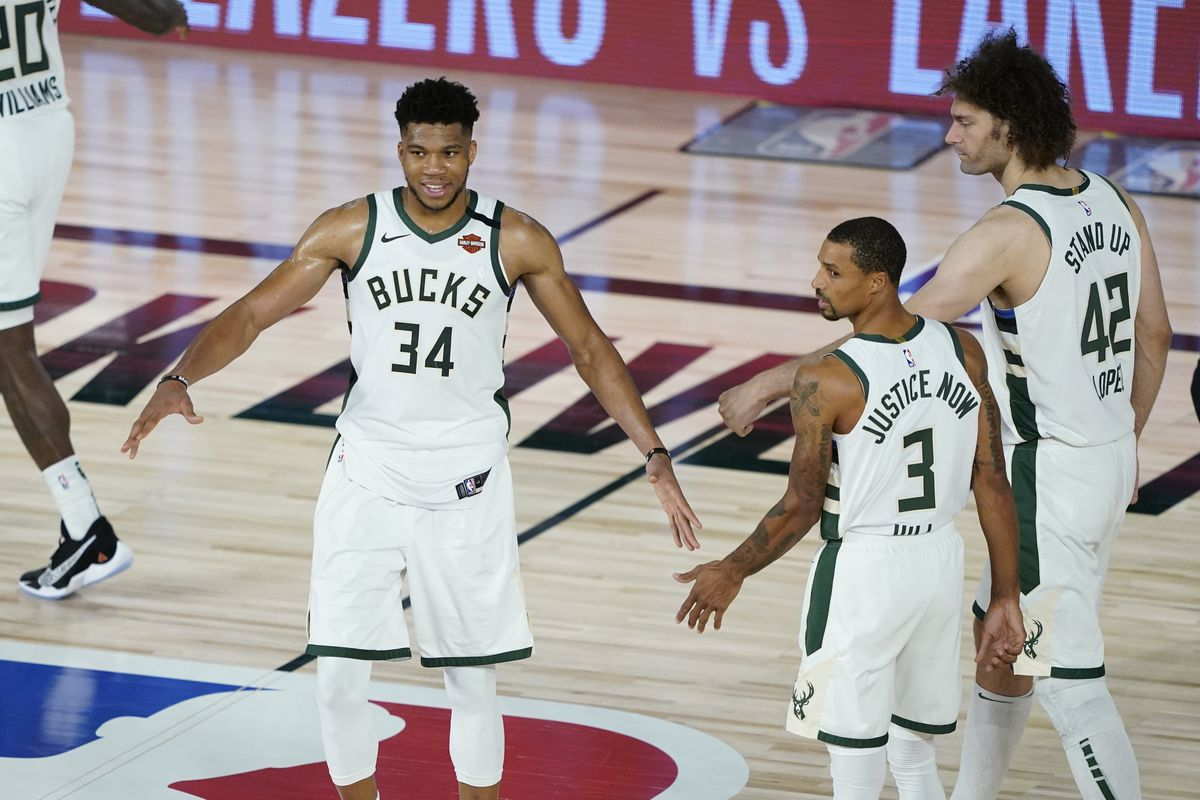 Giannis Antetokounmpo of the Milwaukee Bucks celebrates with George Hill and Robin Lopez the team's win over the Orlando Magic in an NBA basketball first round playoff game on August 20, 2020 in Lake Buena Vista, Florida.