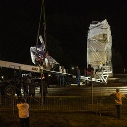 A crane lowers the Christopher Columbus Statue to the ground in Grant Park, Friday, July 24, 2020.