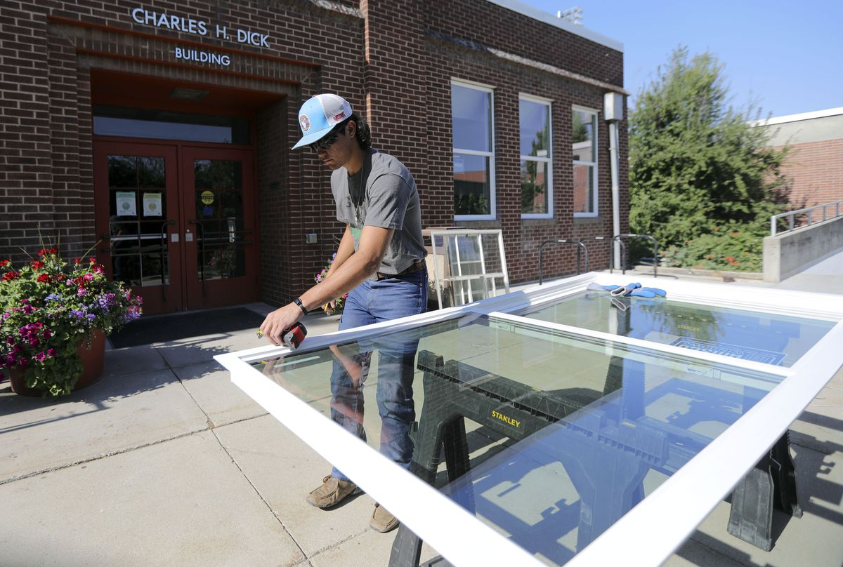 Payton Romero, with City Glass, measures a new window for installation in the Charles H. Dick building at Westminster College in Salt Lake City on Tuesday, June 22, 2021.