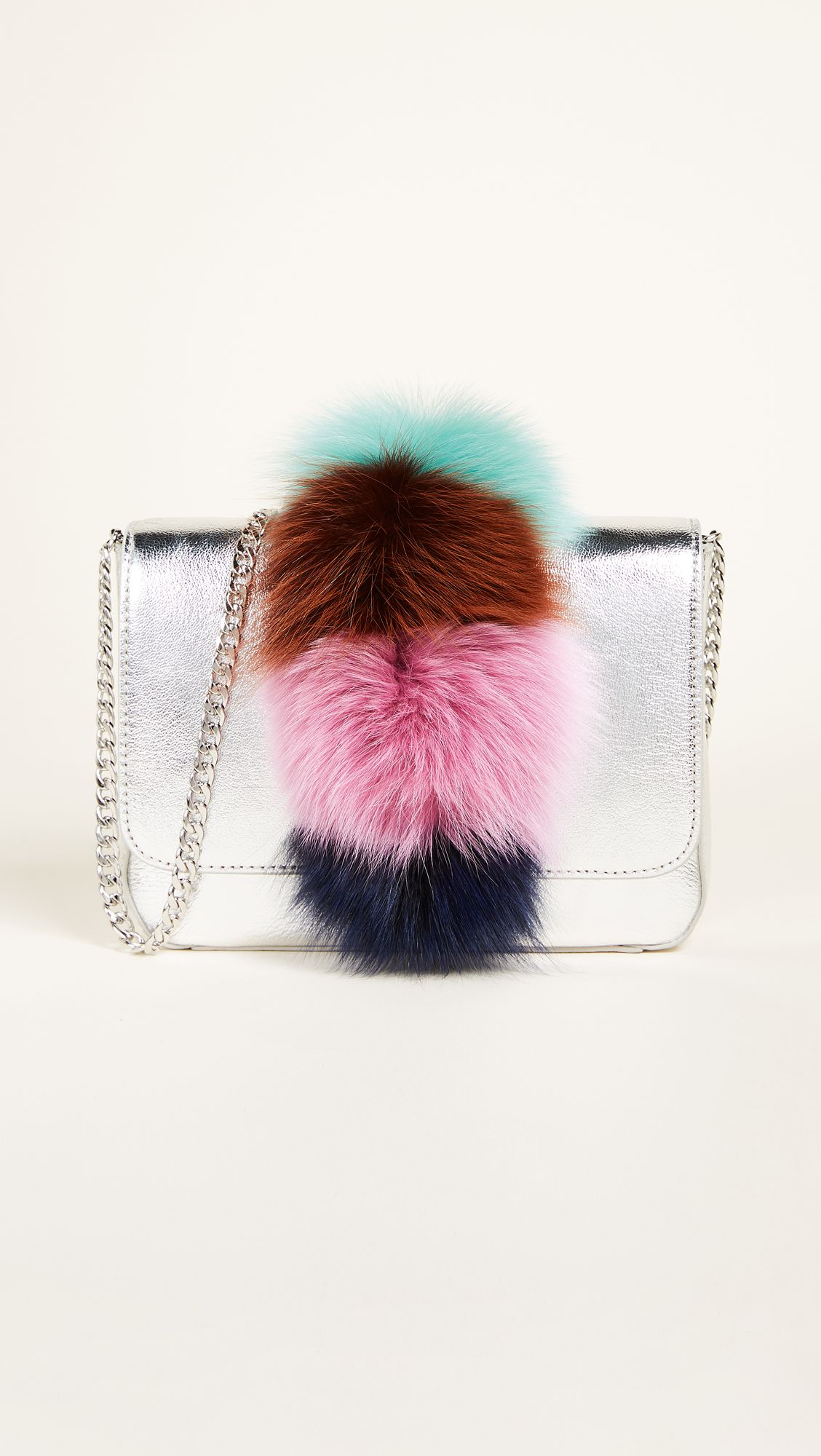 A silver bag with a faux fur handle