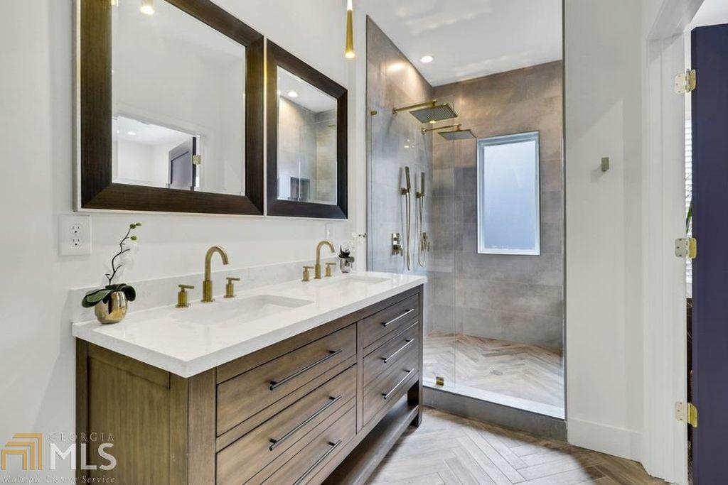A white master bathroom with herringbone floors and two vanities.