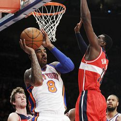 New York Knicks' J.R. Smith (8) passes away from Washington Wizards' Chris Singleton (31) and Jan Vesely (24) during the first half of an NBA basketball game Friday, April 13, 2012, in New York.